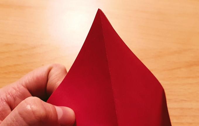 Hand faltet Kopf von Origami Huhn auf