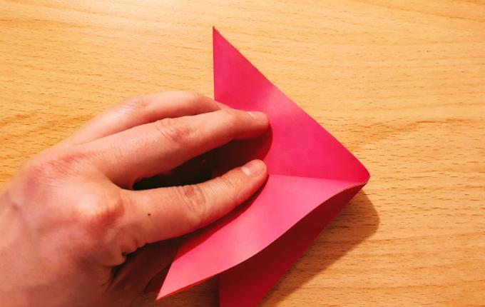 Hand faltet Origami Flügel nach unten links