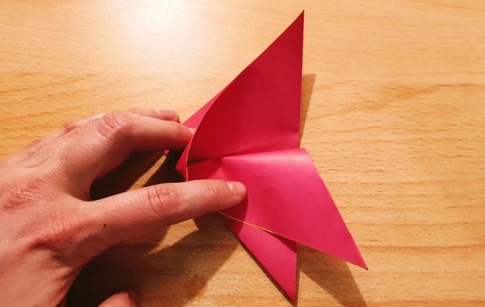 Hand faltet Origami Flügel vom Osterhuhn