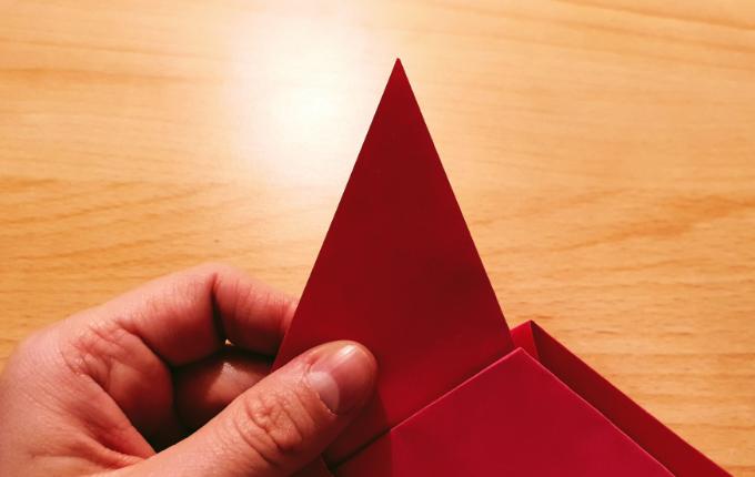 Hand hält fehlenden Kopf von Origami Huhn