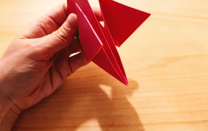 Hand hält Flügelschwanz von Origami Huhn fest