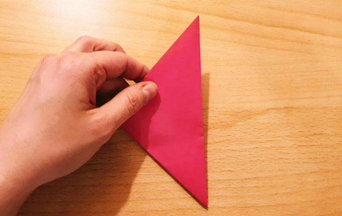 Hand hält gefaltetes Dreieck fest