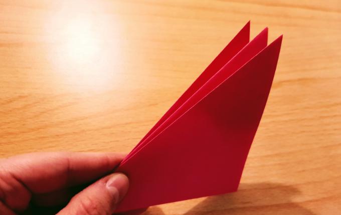 Hand hält Origami Faltung fest