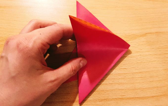 Hand zieht Falte vom Dreieck nach unten