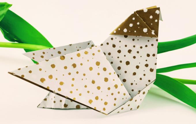liegendes Origami Huhn mit Kopftuch und Blume