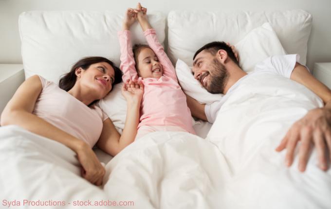 Kind mit Eltern wach im Bett