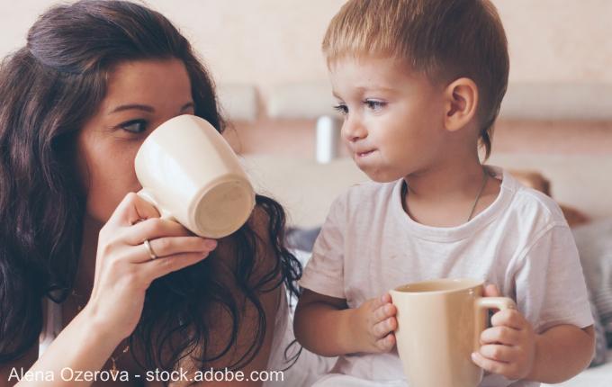 Mutter und Kind schauen sich an und trinken aus Tassen