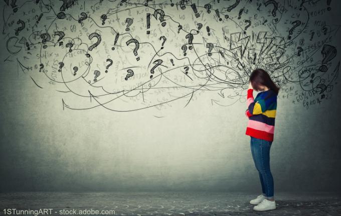 Frau umgeben von vielen Fragezeichen und Gedanken