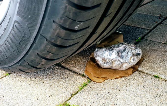 Hinweis mit Stein unter Auto für Schatzsuche