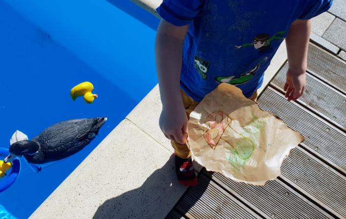 Kind hält am Pool Schnitzeljagd Hinweis in den Händen - Pilz