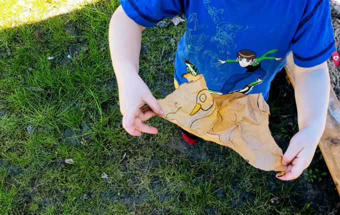 Kind hält Schnitzeljagd Hinweis in den Händen - Ente im Wasser