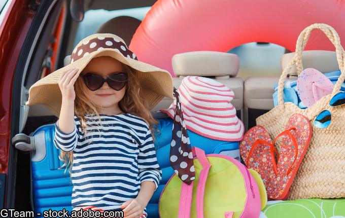 Kind sitzt am Kofferraum mit viel Gepäck