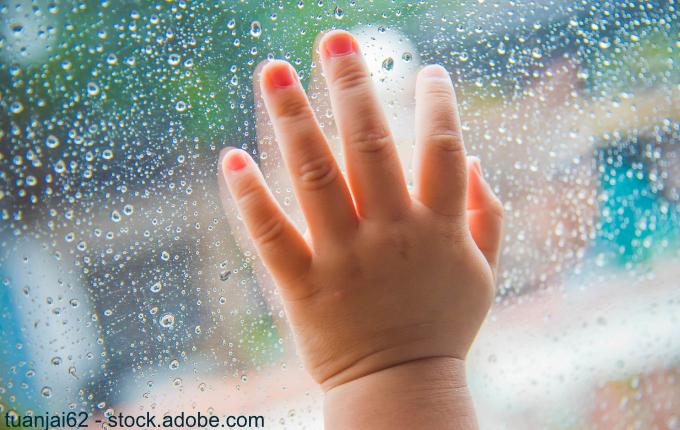 Kinderhand an verregneter Fensterscheibe