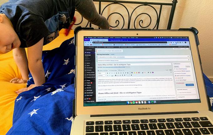 Kind turnt im Bett neben Laptop