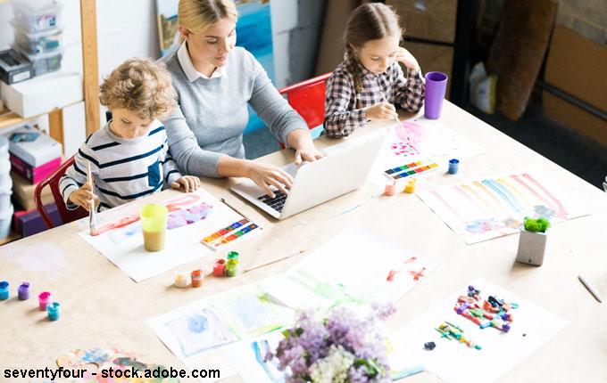 Mama am Laptop mit spielenden Kinder