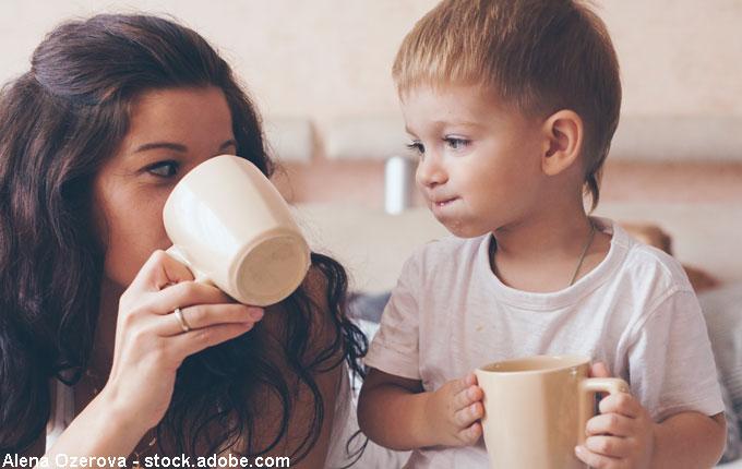 Mama trinkt Kakao mit Kind aus Tassen