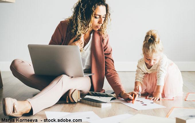 Mutter mit Laptop spielt am Boden mit Kind
