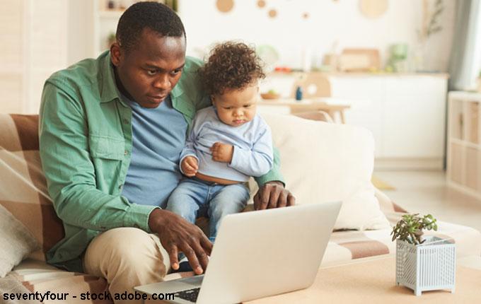 Papa arbeitet mit Kind auf Arm am Laptop