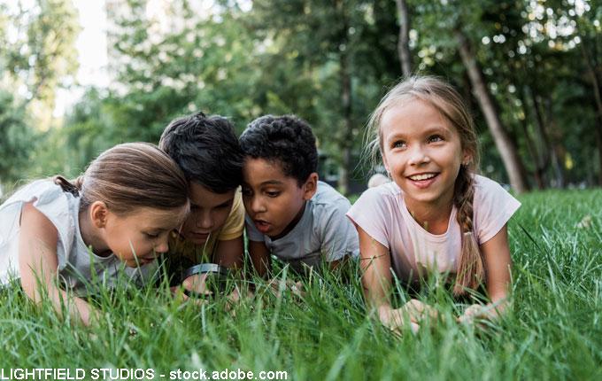 Kind mit Freunden auf der Wiese