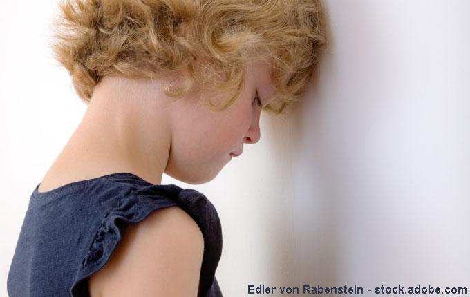 Mädchen lehnt Kopf traurig an Wand