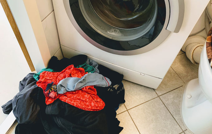 Wäscheberg vor laufender Waschmaschine
