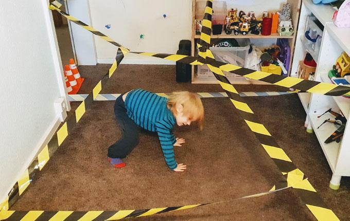 Kind durchquert Laserparcour aus Absperrband