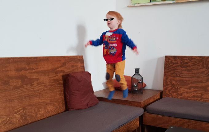 Kind hüpft auf Couch herum