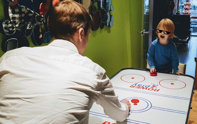 Kind spielt Air Hockey mit Papa