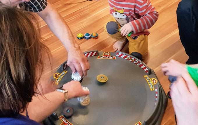 Kind spielt Beyblade mit Familie