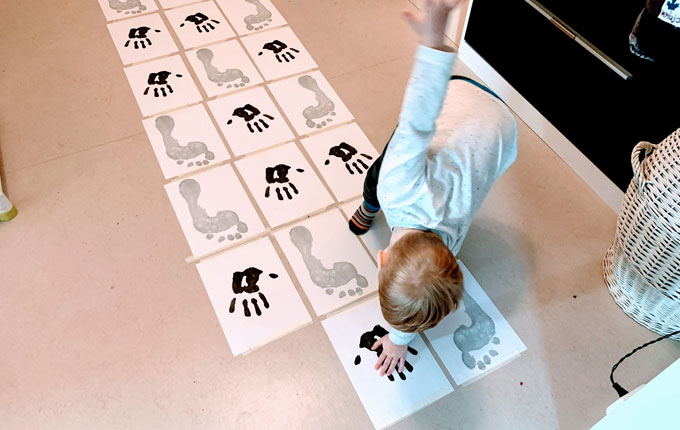 Kind spielt Hüpfspiel