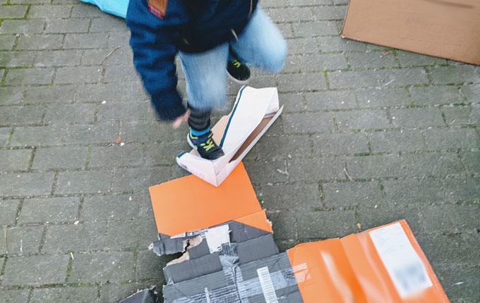 Kind zerstampft Pappkartons