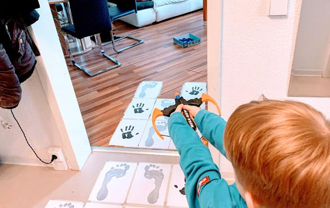 Kind zielt mit Spielzeug Armbrust